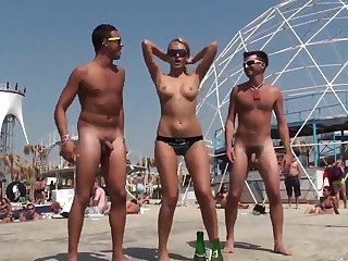 Bared guys on the beach have fun to a young girl